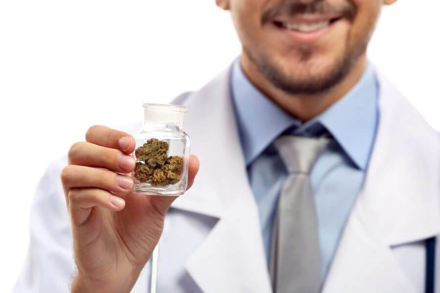 A person in a lab coat holding a small jar of marijuana