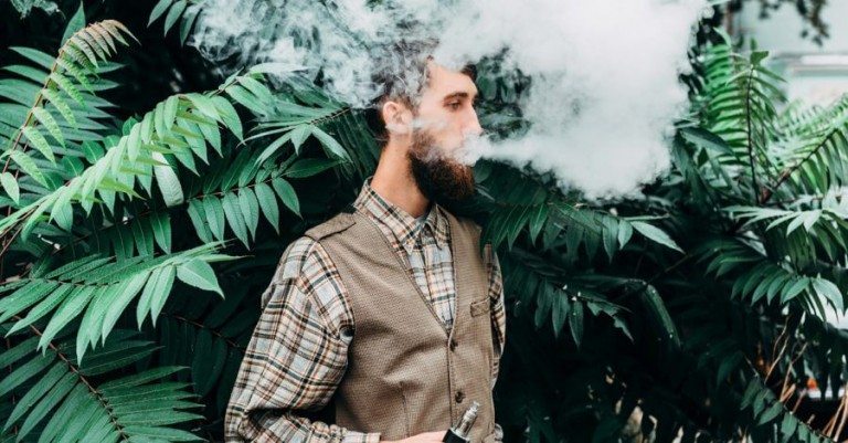 A hipster blowing a giant cloud of vapor